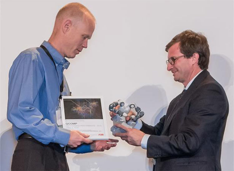 Photo of Greg Whitney of QComp receiving award
